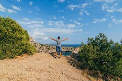 Happy male traveler with arms raised to the sky in the rest is on top of a mountain. Free happy male traveler with arms raised on top of a mountain by the sea in Royalty Free Stock Photos