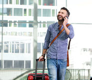 Happy male traveler making a phone call. Portrait of happy male traveler walking with bag and talking on cellphone Stock Photo