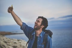 Happy male traveler making selfie at the seaside. Excited young man is taking photo of himself on mobile phone. He is standing on cliff near the sea and laughing Royalty Free Stock Image