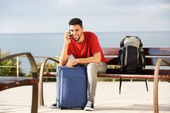 Happy male traveler sitting on bench with bags and talking on mobile phone. Portrait of happy male traveler sitting on bench with bags and talking on mobile Royalty Free Stock Image