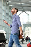 Happy male traveler walking with bag and cellphone. Side portrait of happy male traveler walking with bag and cellphone Stock Photos