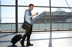 Happy male traveler walking with bags and cellphone. Full body portrait of a happy male traveler walking with bags and cellphone Stock Images