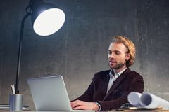 Happy male typing in notebook computer. Portrait of outgoing bearded man using laptop while locating at desk during job. Labor with digital device concept Royalty Free Stock Photography
