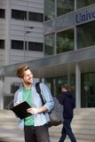 Happy male university student standing on campus. Portrait of a happy male university student standing on campus with pen and notepad Stock Photo