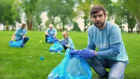 Happy male volunteer putting rubbish in garbage bag and smiling, responsibility stock footage