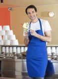 Happy Male Waiter Preparing Ice Cream At Parlor Stock Photo