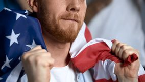 Happy male waving American flag, watching sports competition, cheering team. Stock photo stock images