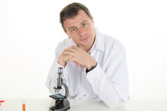 Happy male  wearing lab coat while sitting in clinic Royalty Free Stock Images