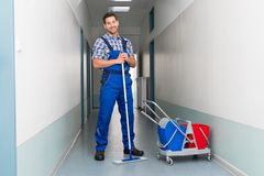 Happy male worker with broom cleaning office corridor Royalty Free Stock Photography