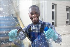 Male Worker Cleaning Glass With Squeegee. Happy Male Worker Cleaning Glass With Squeegee And Spray Bottle Stock Photos