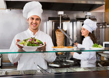 Happy male worker serving customer with smile. At shawarma place Royalty Free Stock Photo