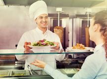 Happy male worker serving customer with smile at shawarma place. Happy friendly smiling male worker serving customer with smile at shawarma place Royalty Free Stock Photography