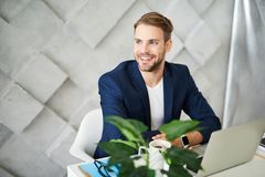 Happy male working at computer and relaxing. Waist up portrait of delighted businessman drinking coffee at desktop. He is looking sideways and sitting at laptop Stock Photo