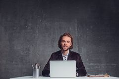 Happy male working with laptop at table. Portrait of cheerful unshaven employer typing in notebook computer while locating at desk. Occupation concept Stock Photos