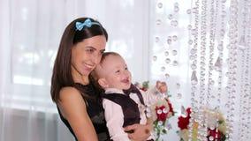 Happy mama speelt met haar kleine zoon in een heldere kamer met mooie kroonlui stock videobeelden