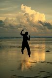 Happy man. A happy man jumping in the air on the beach, in silhouette Stock Images