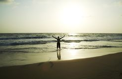 Happy man. Silhouette on the sunsets sea stock photography