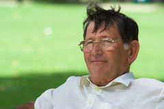Happy man. Portrait of a happy older senior man sitting in a park royalty free stock image