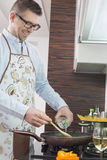 Happy man adding white wine to saucepan while cooking in kitchen Royalty Free Stock Images