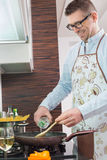 Happy man adding white wine to saucepan while cooking in kitchen stock photography