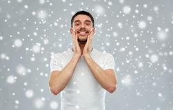 Happy man applying aftershave or cream to face Royalty Free Stock Image