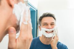 Happy man applying shaving cream Royalty Free Stock Image