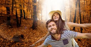 Happy man with arms outstretched carrying woman on back in forest during autumn Royalty Free Stock Photography