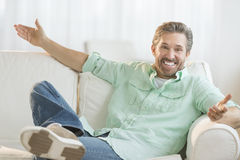 Happy Man With Arms Outstretched On Sofa Royalty Free Stock Image