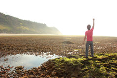 Happy man with arms raised on beach Stock Photography