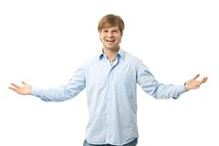 Happy man with arms wide open. Happy young man standing with arms wide open, laughing. Isolated on white Royalty Free Stock Image