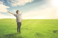 Happy man with arms wide open enjoying spring on green meadow royalty free stock photos