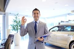 Happy man at auto show or car salon. Auto business, car sale, consumerism, gesture and people concept - happy man with clipboard showing thumbs up at auto show royalty free stock image