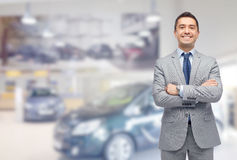 Happy man at auto show or car salon. Business, car sale, consumerism and people concept - happy man over auto show or salon background stock photography