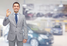 Happy man at auto show or car salon. Business, car sale, consumerism and people concept - happy man over auto show or salon background Royalty Free Stock Photography