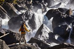 Happy man with backpack enjoying amazing waterfall Travel Lifestyle and success concept vacations into the wild nature royalty free stock image