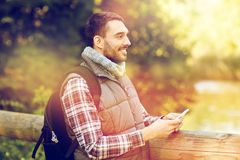 Happy man with backpack and smartphone outdoors. Travel, tourism, hike, technology and people concept - happy man with backpack and smartphone outdoors royalty free stock photography