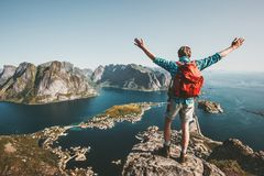 Happy Man backpacker raised hands on mountain top. Lifestyle travel adventure outdoor summer vacations tourist enjoying aerial view in Norway stock image