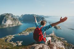 Happy Man backpacker raised hands traveling. Sitting on cliff edge lifestyle adventure outdoor summer vacations enjoying aerial sea view stock photos