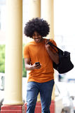 Happy man with bag looking at cellphone in the city Royalty Free Stock Photo