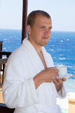 Happy man in bathrobe with cup of coffee standing on balcony Stock Images