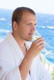 Happy man in bathrobe drinking champagne on balcony Stock Photo