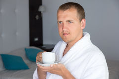 Happy man in bathrobe drinking coffee in hotel room Stock Photography