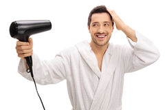 Happy man in a bathrobe drying his hair with a hairdryer. Isolated on white background Royalty Free Stock Image