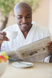 Happy man in bathrobe having coffee on terrace Stock Photo