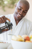 Happy man in bathrobe pouring coffee on terrace Stock Image