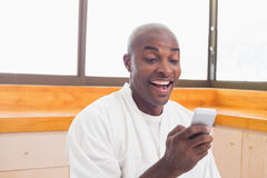 Happy man in bathrobe sending a text Stock Images