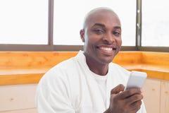 Happy man in bathrobe sending a text Royalty Free Stock Photos