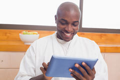 Happy man in bathrobe using tablet pc Royalty Free Stock Images