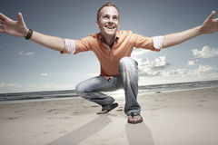 Happy man on the beach. With his arms extended royalty free stock images