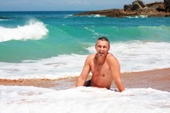 Happy man on the beach in Suances, Spain. Cheerful man sitting in the water on the beach in Suances, Spain stock photography